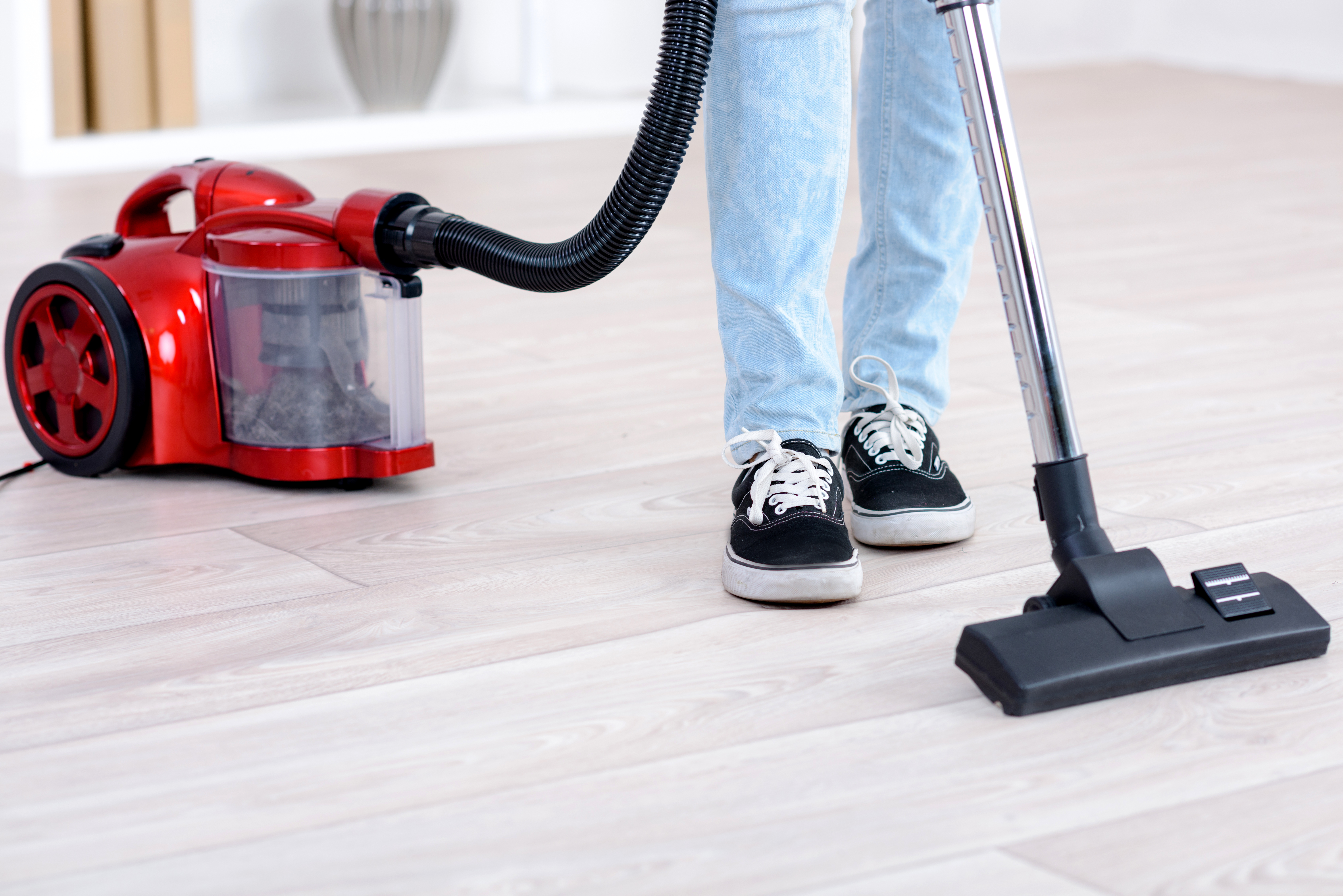 Red vacuum cleaner being used