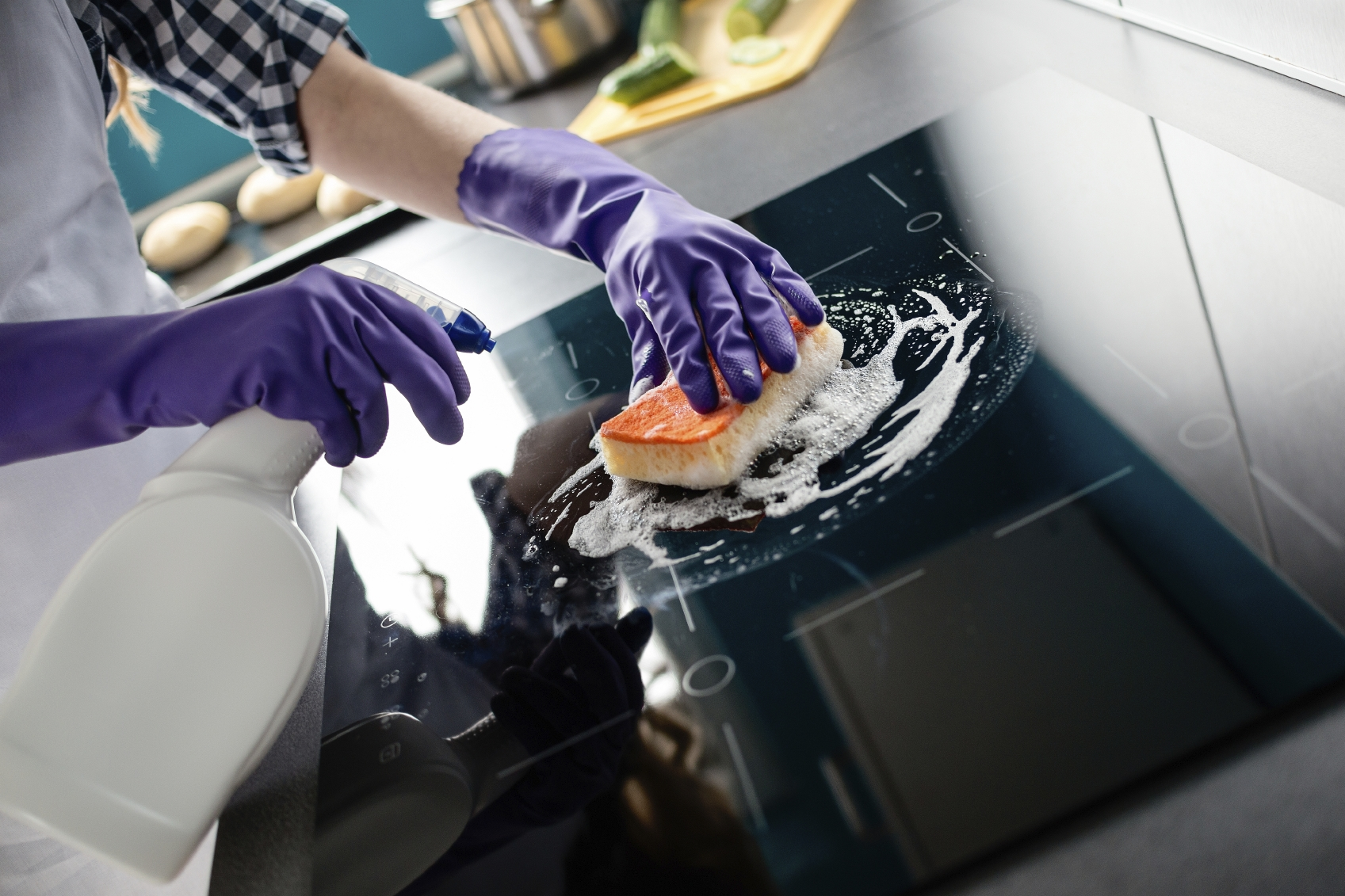 Woman's hands cleaning kitchen top in purple rubber protective gloves