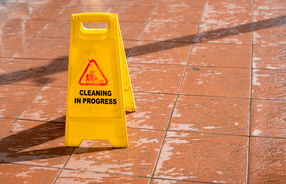 A yellow cleaning in process sign on the orange floor.