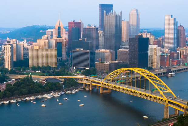 Pittsburgh skyline in the early morning featuring a yellow bridge